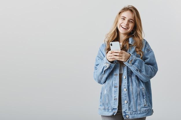 Mulher sorridente e atraente usando telefone celular com expressão alegre