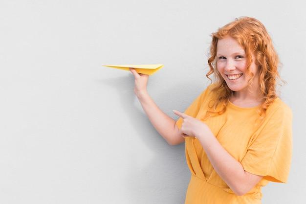 Mulher sorridente e avião de papel