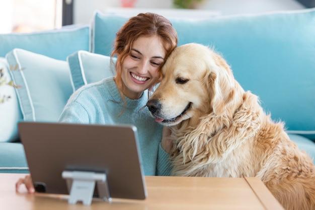 Mulher sorridente e cachorro com tablet tiro médio