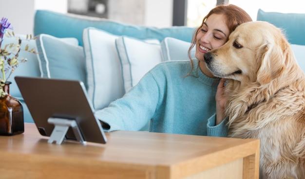 Mulher sorridente e cachorro com tablet
