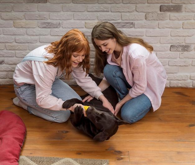 Mulher sorridente e cachorro no chão