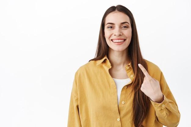 Mulher sorridente e confiante apontando para si mesma com um rosto orgulhoso e determinado, que se autopromove, mostrando seus novos dentes brancos, em pé sobre a parede do estúdio