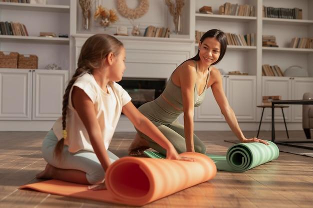 Mulher sorridente e criança com tapete de ioga, tiro completo