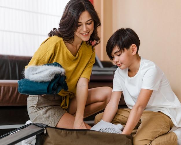 Mulher sorridente e criança fazendo malas