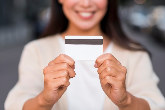 Mulher sorridente e desfocada segurando um cartão de crédito