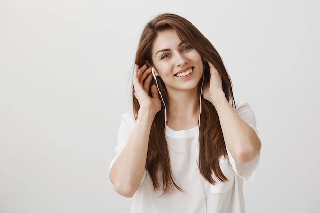 Mulher sorridente e despreocupada ouvindo música em fones de ouvido