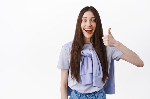 Mulher sorridente e divertida com cabelo comprido, mostra o polegar em aprovação, parece impressionada, elogia o bom trabalho, parada satisfeita contra a parede branca