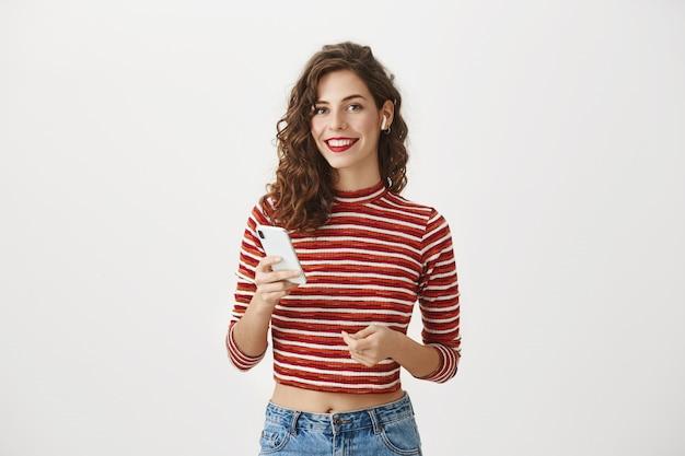 Mulher sorridente e elegante usando telefone celular, ouvindo música em fones de ouvido sem fio