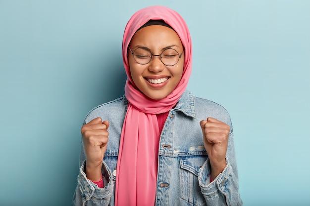 Mulher sorridente e encantadora usa o tradicional véu árabe, fecha os punhos, comemora conquistas, comemora a vitória