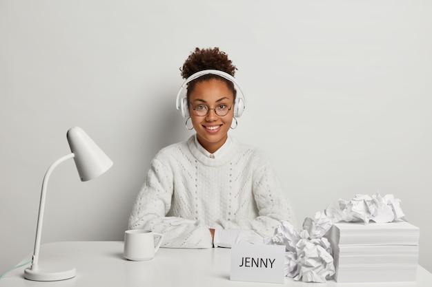 Mulher sorridente e encaracolada com um suéter branco, usa capacete nas orelhas e ouve música relaxante