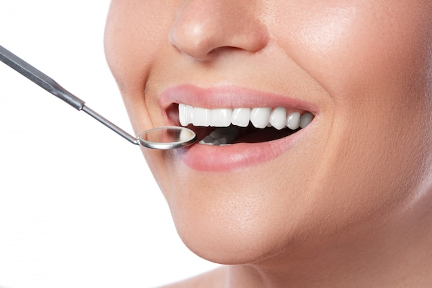 Mulher sorridente e espelho dental