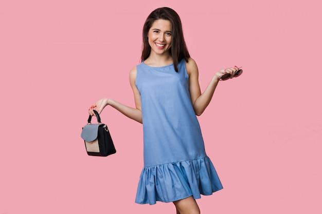 Mulher sorridente e feliz com vestido de algodão azul de verão posando em fundo rosa, segurando bolsa e óculos escuros, estilo de férias, jovem e bonita