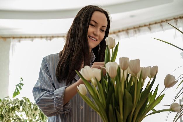 Mulher sorridente e feliz de camisa azul cuidando de tulipas brancas