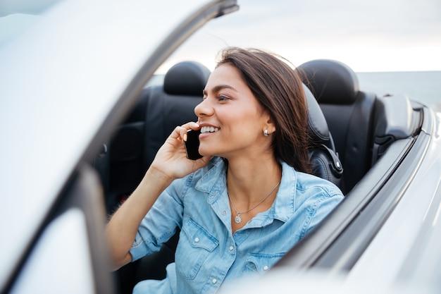 Mulher sorridente e feliz dirigindo um carro e falando no celular