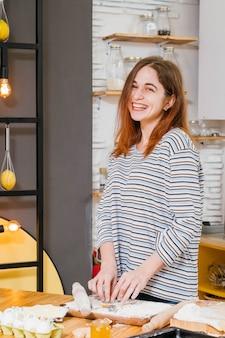 Mulher sorridente e feliz fazendo biscoitos na cozinha