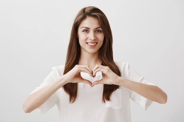 Mulher sorridente e feliz mostrando gesto de coração