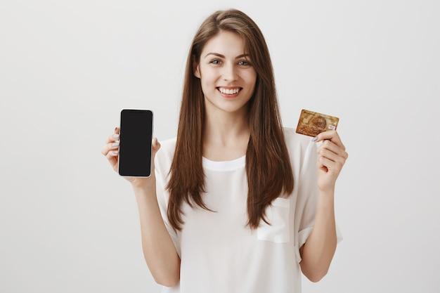 Mulher sorridente e feliz mostrando o visor do celular e o cartão de crédito. aplicativo de promoção de compras