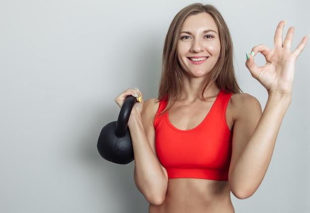 Mulher sorridente e feliz segurando o kettlebell com uma mão em fundo preto