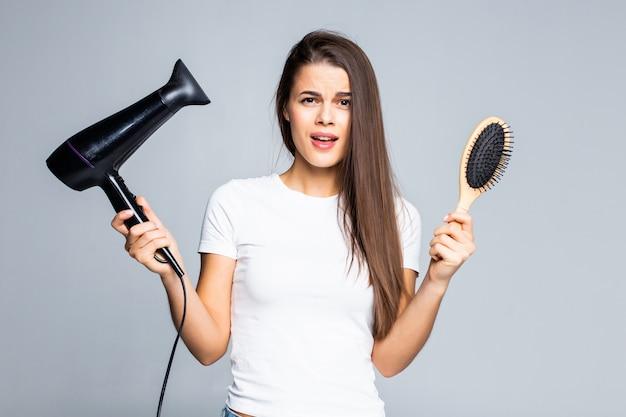Mulher sorridente e feliz, segurando o secador de cabelo na mão esquerda e escova na mão direita com o pente isolado no branco