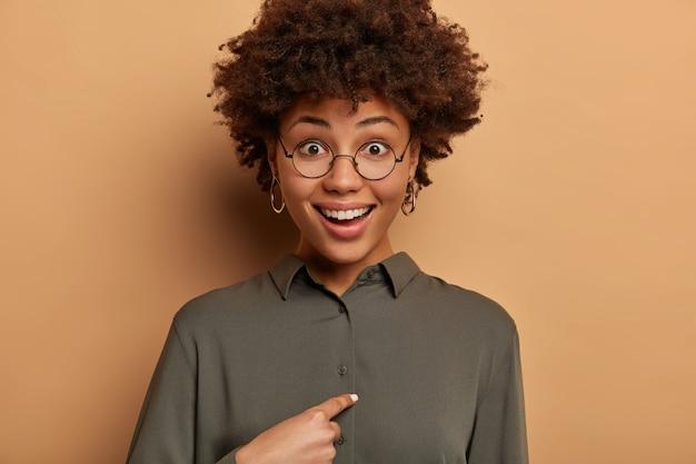 Mulher sorridente e feliz surpreende que alguém cite seu nome, aponta para si mesma, não esperava ganhar ou ser escolhida, pergunta ao chefe se exatamente ela foi promovida, usa óculos redondos e camisa.