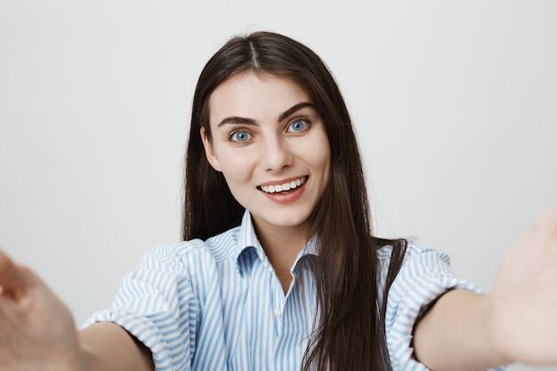 Mulher sorridente e feliz tirando uma selfie ou videochat
