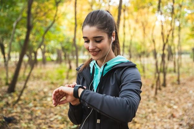Mulher sorridente e fitness ouvindo música com fones de ouvido, verificando o smartwatch, enquanto estava no parque