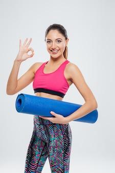 Mulher sorridente e fitness segurando um tapete de ioga e mostrando um sinal de ok com os dedos
