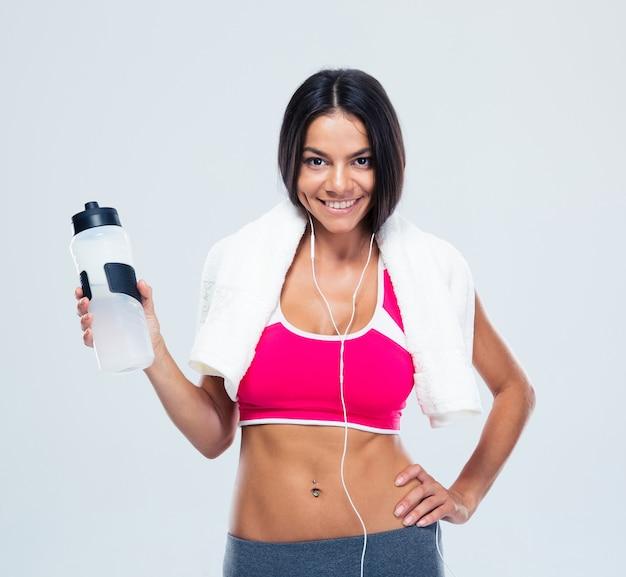 Mulher sorridente e fitness segurando uma garrafa com água