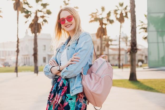 Mulher sorridente e flertando andando na rua da cidade com saia estampada elegante e jaqueta jeans grande e óculos de sol rosa