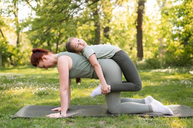 Mulher sorridente e garota treinando juntas