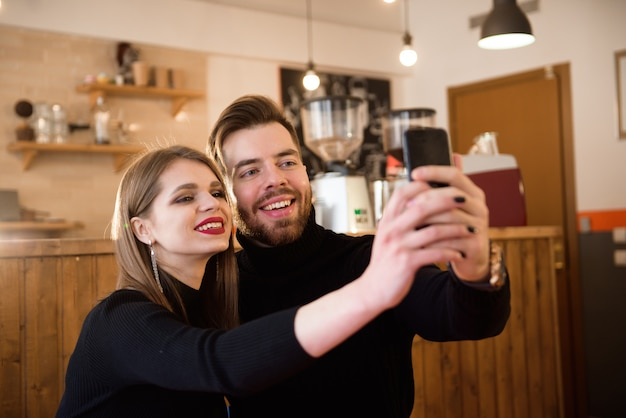Mulher sorridente e homem bonito, bebendo café, usando telefone celular enquanto passar o tempo em uma cafeteria.