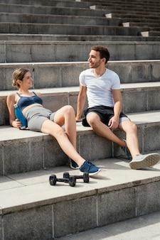 Mulher sorridente e homem descansando nos degraus enquanto se exercitam