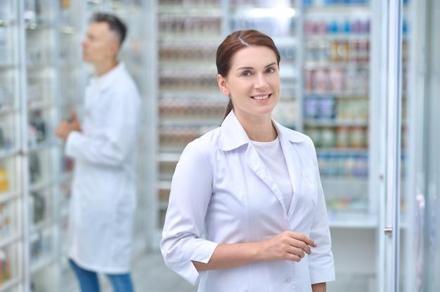 Mulher sorridente e homem sério trabalhando em farmácia