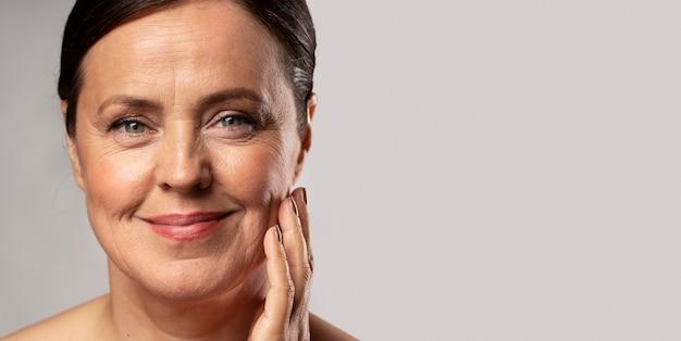 Mulher sorridente e idosa com maquiagem, posando com a mão no rosto e copie o espaço