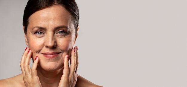 Mulher sorridente e idosa com maquiagem, posando com as mãos no rosto e copie o espaço