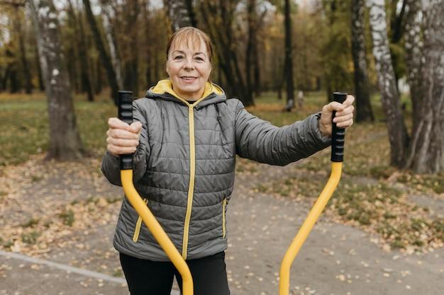 Mulher sorridente e idosa malhando ao ar livre