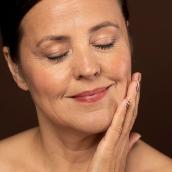 Mulher sorridente e idosa posando com maquiagem