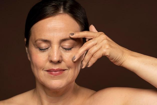 Mulher sorridente e idosa posando maquiada e mostrando as unhas