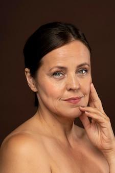 Mulher sorridente e idosa posando para uma foto de beleza com maquiagem