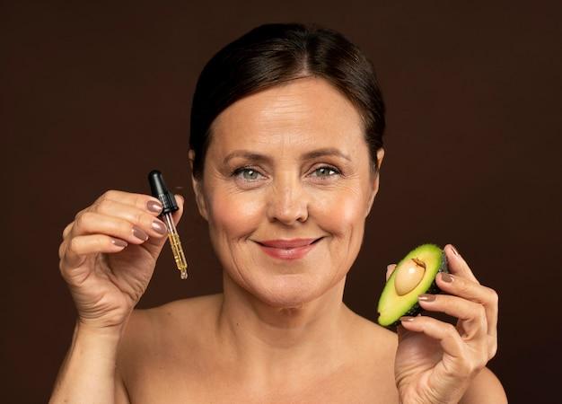 Mulher sorridente e idosa segurando metade de um abacate com soro