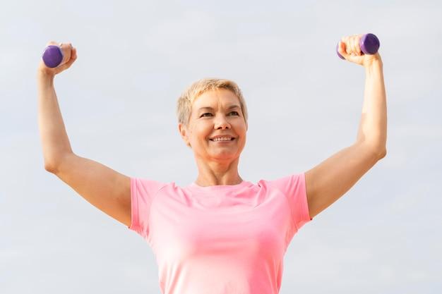 Mulher sorridente e idosa segurando pesos enquanto se exercita