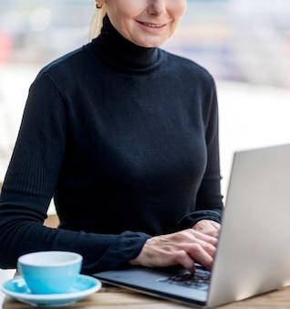 Mulher sorridente e idosa tomando café ao ar livre enquanto trabalha no laptop