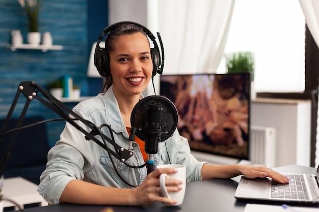 Mulher sorridente e influenciadora sentada em frente à câmera gravando um vídeo para um blog de moda. blogger digital vlogger transmitindo talk show em estúdio usando fones de ouvido e microfone profissional para podcast