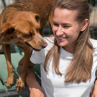Mulher sorridente e lindo cão de resgate no abrigo