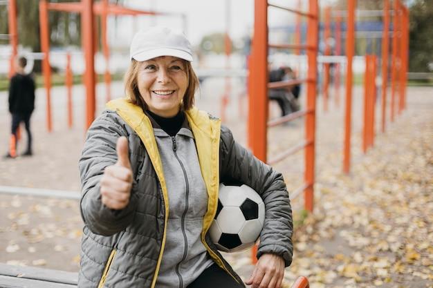 Mulher sorridente e mais velha segurando uma bola de futebol e levantando os polegares enquanto se exercita
