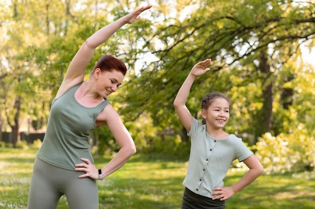 Mulher sorridente e menina treinando