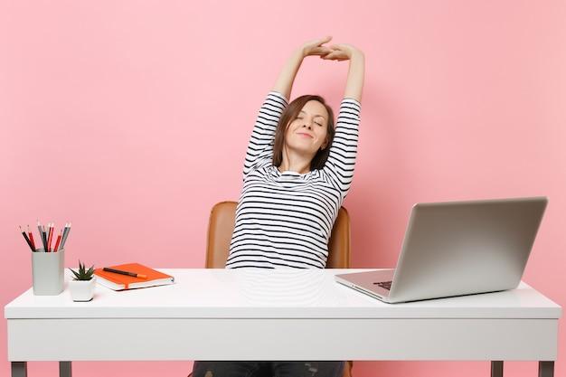 Mulher sorridente e relaxada com os olhos fechados, descansando esticando as mãos, sente-se no trabalho na mesa branca com o laptop pc contemporâneo isolado no fundo rosa pastel. conceito de carreira empresarial de realização. copie o espaço.