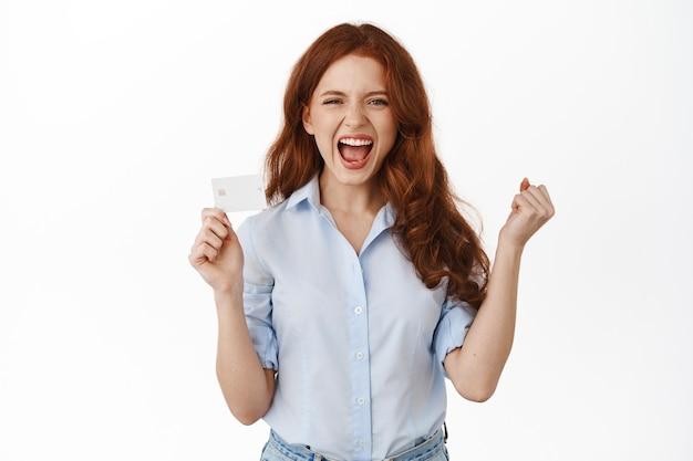 Mulher sorridente e ruiva segurando um cartão de crédito em branco