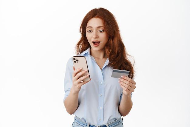 Mulher sorridente e ruiva segurando um smartphone e um cartão de crédito em branco