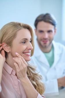 Mulher sorridente e satisfeita admirando seu novo aparelho auditivo